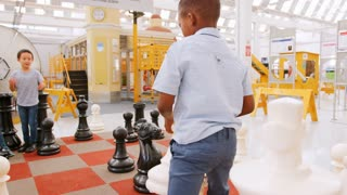 School kids playing giant chess at a science activity centre