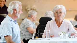 Senior Couple Being Served With Meal By Carer In Dining Room Of Retirement Home