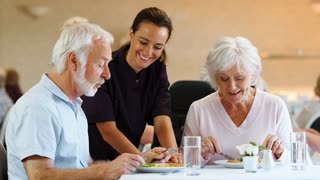 Senior Couple Eating Meal And Talking With Carer In Retirement Home