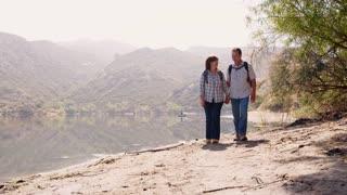 Senior couple hiking by a mountain lake