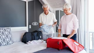 Senior Couple In Bedroom Packing Suitcase For Vacation