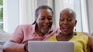 Senior Couple Using Laptop To Connect With Family For Video Call