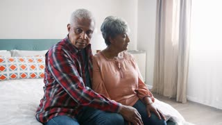 Senior Man Comforting Woman With Depression In Bedroom At Home