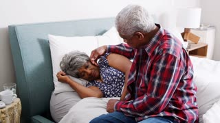 Senior Man Comforting Woman With Depression Lying In Bed At Home