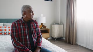 Senior Man Suffering With Depression Sitting In Bedroom At Home