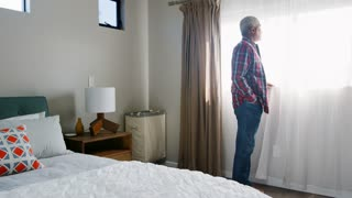 Senior Man Suffering With Depression Standing By Bedroom Window At Home