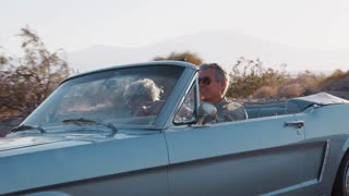 Senior white couple driving classic convertible on highway