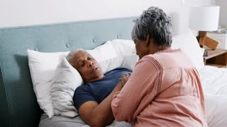 Senior Woman Comforting Man With Illness Lying In Bed At Home