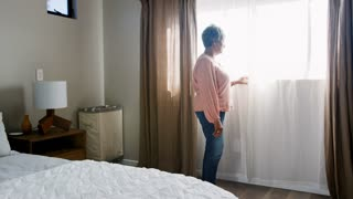 Senior Woman Suffering With Depression Standing By Bedroom Window At Home