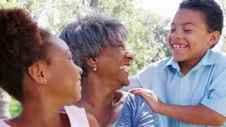 Slow Motion Portrait Of Grandmother With Grandchildren Relaxing In Park