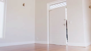 Slow Motion Shot Of Couple Opening Door And Walking In Empty Lounge Of New Home
