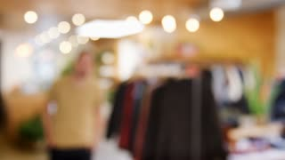 Smiling Hispanic man walks into focus in a clothes shop