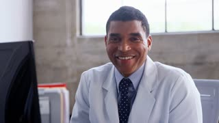 Smiling mixed race doctor in lab coat sitting in the office