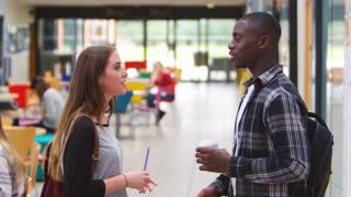 Student Couple Talking In Communal Area Of Busy College Campus