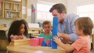 Teacher And Pupils Using Wooden Shapes In Montessori School