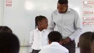 Teacher and schoolgirl in front of elementary school class
