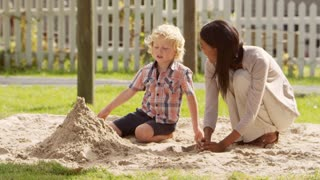 Teacher At Montessori School Playing With Male Pupil In Sand Pit
