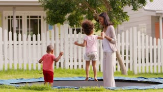 Teacher At Montessori School Playing With Pupils On Trampoline