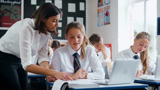 Teacher Helping Female Pupil Using Computer In Classroom