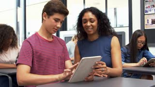 Teacher helping teenage schoolboy use tablet computer