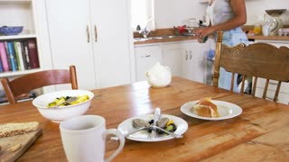 Teenage Girl Wiping Down Breakfast Table In Kitchen After Meal