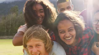 Teenage school friends smiling to camera outdoors, close up