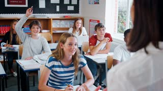 Teenage Students Raising Hand To Ask Question In Classroom