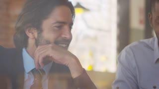 Three Businessmen Meeting In Coffee Shop Shot Through Window