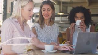 Three Businesswomen Meeting In Coffee Shop Shot Through Window
