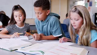 Three pupils working together in elementary school lesson
