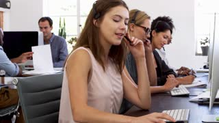 Three women with headsets on working at computers in office