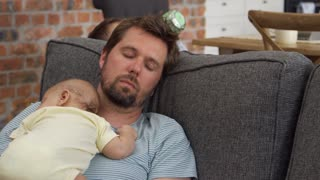 Tired Father With Baby Son Sleeping On Sofa Together