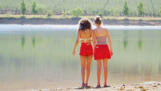 Two adult girlfriends walking by a  lake back view