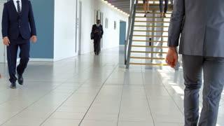 Two Businessmen Meet In Corridor Of Busy Modern Office