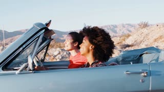 Two female friends driving an open car on a desert highway