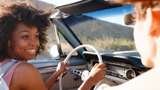 Two female friends driving in an open top car, close up