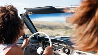Two female friends driving in an open top classic car