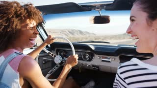 Two female friends driving on a desert road in a classic car