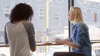 Two Female Friends Meeting In Coffee Shop Shot In Slow Motion