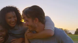 Two smiling couples piggybacking outdoors, close up