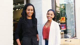 Two young women smiling to camera outside their clothes shop