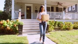 Woman Putting Cardboard Into Recycling Bin On Suburban Street
