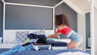 Woman Trying To Close Full Holiday Suitcase In Bedroom