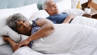Worried Senior Woman Waking Up Next To Husband In Morning