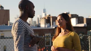 Young adult couple talking together on a New York rooftop