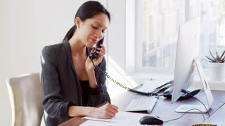 Young Asian woman on the phone smiling at her office desk