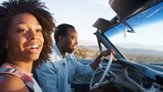 Young black couple driving in open car, close up, side view