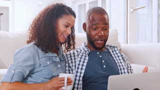 Young black couple sitting on sofa looking at computer