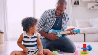 Young black dad and his young daughter playing instruments