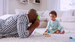 Young black father lying on floor playing with his young son